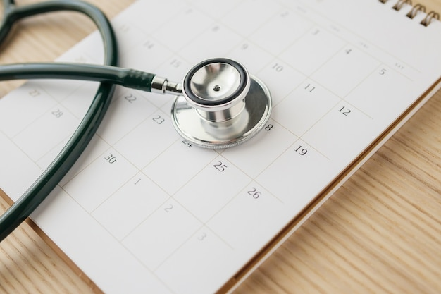 Stethoscope with calendar page date on wood table wall doctor appointment medical concept