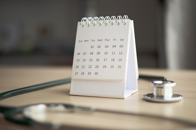 Stethoscope with calendar page on wood table
