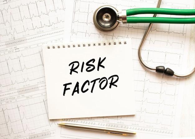 Стетоскоп с кардиограммой и блокнотом с текстом фактор риска.
