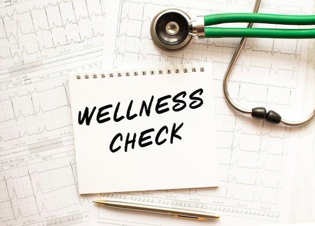 Стетоскоп с кардиограммой и блокнотом с текстом wellness check