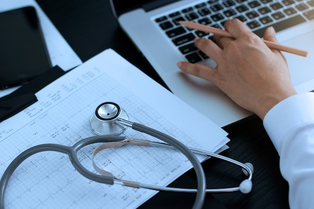 Stethoscope with cardiogram and doctor using a laptop