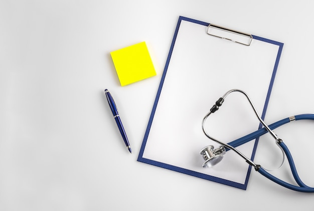 Stethoscope with clipboard, pen and post-it, top view