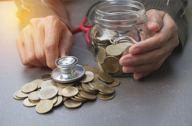 Stethoscope with coins in jar with money stack, concept finance, accounting, business.