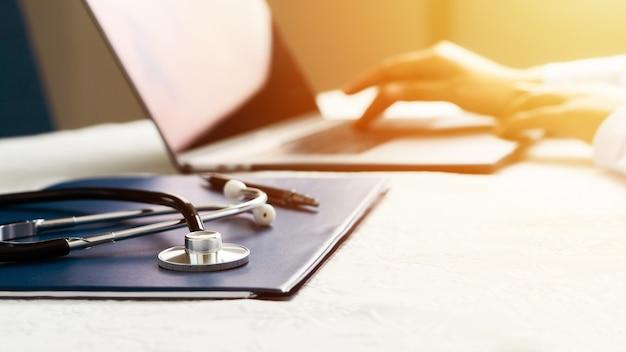 Стетоскоп с файлом и ноутбуком на столе, доктор, работающий в больнице, пишет рецепт, здравоохранение и медицинская концепция