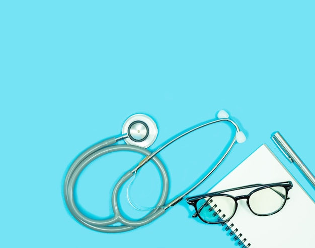 Stethoscope with glasses on blank notebook and pen on blue background