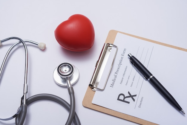 Stethoscope with heart. stethoscope and red heart on wooden table. hospital life insurance concept. world heart health day idea. medicine or pharmacy concept. empty medical form ready to be used.