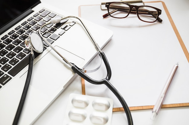 Stethoscope with laptop; clipboard; eyeglasses and pen on clipboard