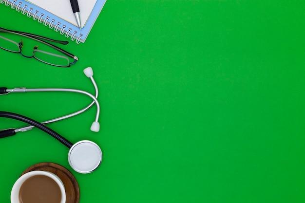 ノートブック、ペン、コーヒー、白い紙、メガネ、緑の背景に薬の瓶と聴診器。医学的背景の概念。
