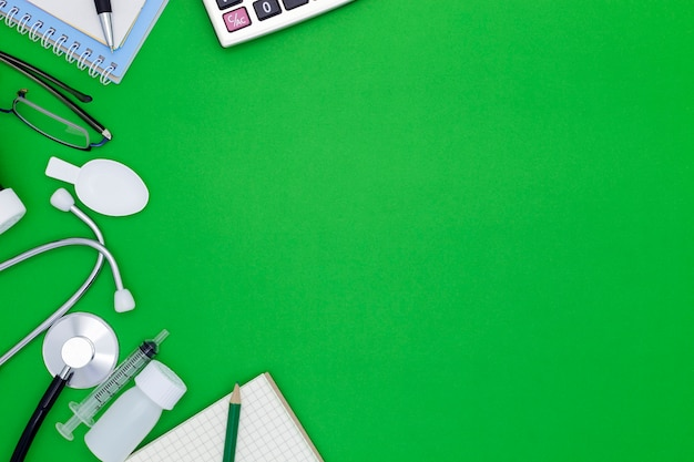 Stethoscope with notebook, pen, white paper, glasses, bottle of medicine, feeding syringe on green background with copyspace