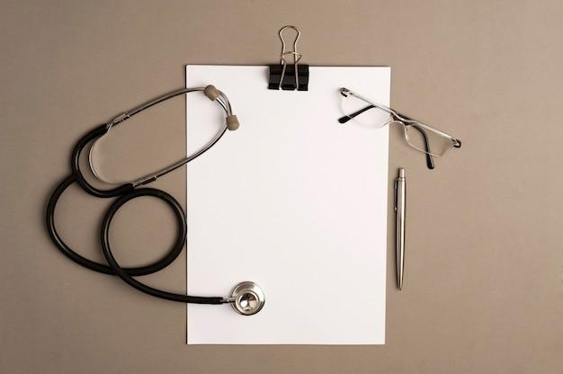 Стетоскоп с блокнотом, очками и ручкой, серый фон с копией пространства.