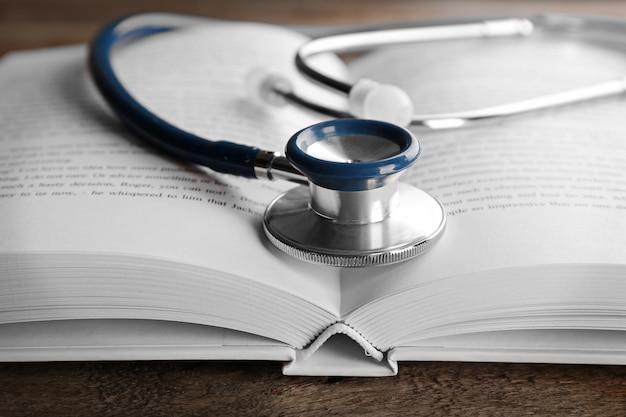木製のテーブルに開いた本と聴診器。医学文献の概念