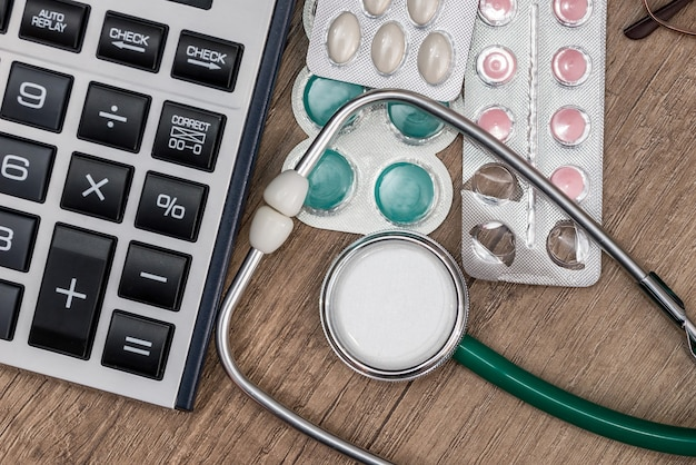 Stethoscope with pills and calculator on wooden table