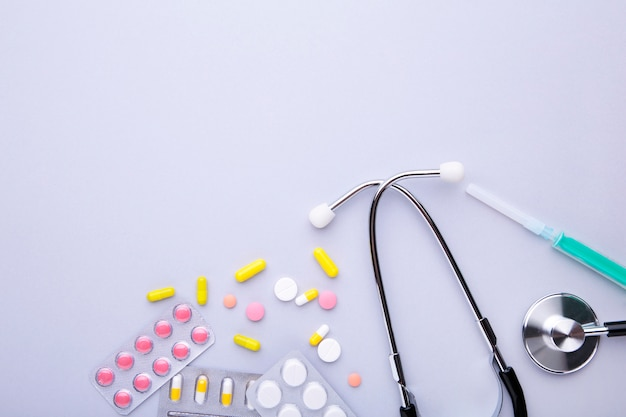 Stethoscope with pills on grey background. top view with place for your text.
