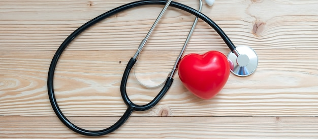 Stethoscope with red heart shape on wooden background.