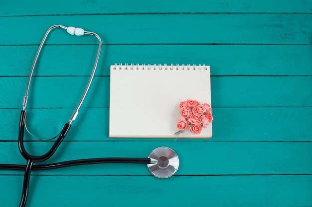 Stethoscope with small flowers and open notebook