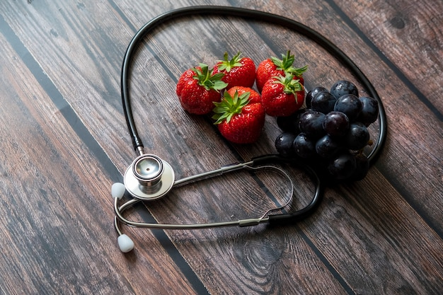 Stethoscope with strawberries and black seedless grape on top of wooden table.