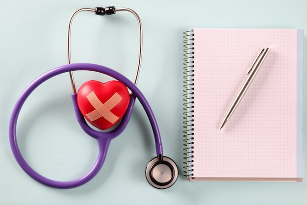 Stethoscope with toy heart and pen with notebook lying on blue table. medical consultations concept