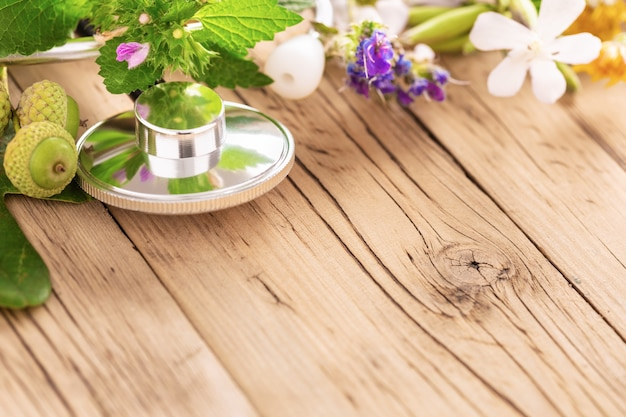 木製のテーブルにさまざまな植物、癒しのハーブの葉と健康的なオイルを備えた聴診器