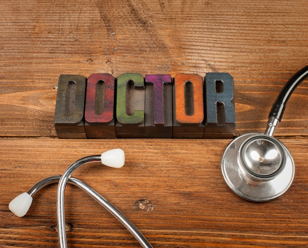 Stethoscope on wood and word doctor in letterpress type