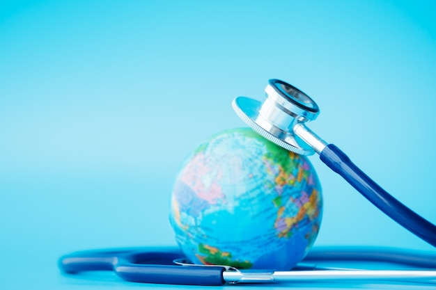 Stethoscope wrapped around globe on blue backgrounds.