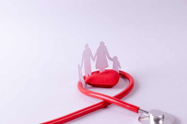Stethoscope wrapped around red heart and family figure on white paper