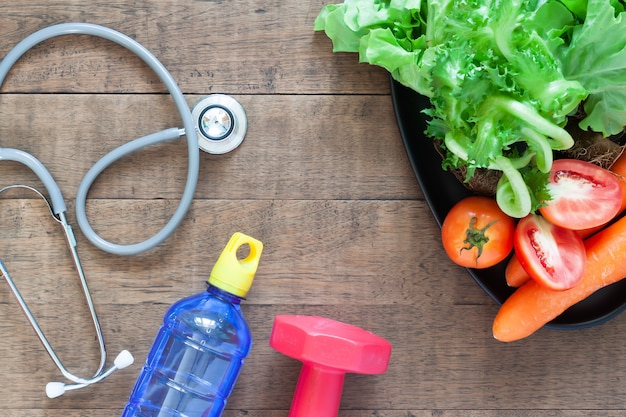 Stethoscopes and fresh vegetables on wood