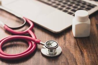 Stethoscopes with notebook and bottle of drug on table