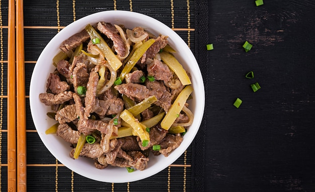 Stew beef, pieces of beef stewed in soy sauce with spices with pickled cucumber in asian style. top view, overhead, flat lay