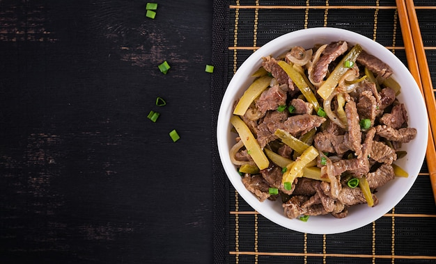Тушеная говядина, кусочки говядины, тушенные в соевом соусе со специями, с маринованным огурцом по-азиатски. вид сверху, сверху, плоская планировка