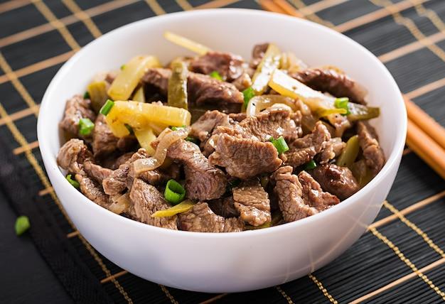 Тушеная говядина, кусочки говядины, тушенные в соевом соусе со специями, с маринованным огурцом по-азиатски.