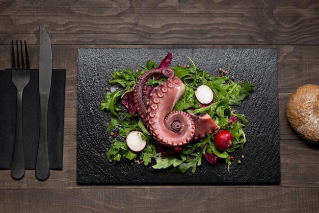 Тушеные щупальца осьминога с салатом на каменной тарелке на деревянном столе. вид сверху.