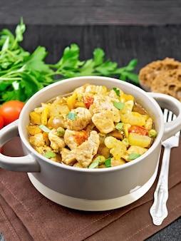 鶏の胸肉、トマト、茎のセロリ、ニンジン、グリーンピース、玉ねぎのシチュー、木の板の背景に茶色のナプキンのテリーヌ