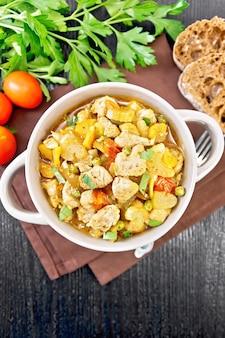鶏の胸肉、トマト、茎のセロリ、ニンジン、グリーンピース、玉ねぎのシチューをナプキンに乗せて、上から暗い木の板にかけます。