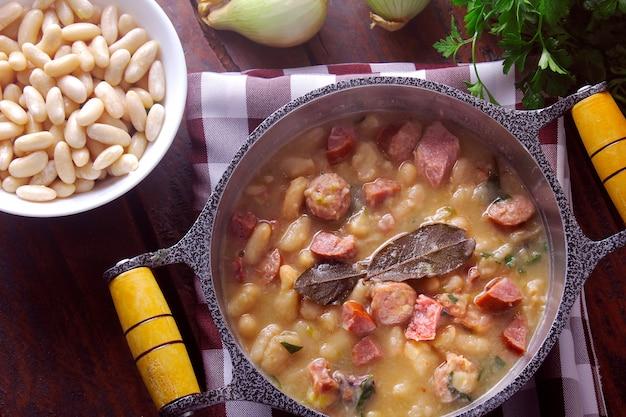 ソーセージ、野菜、スパイス、ハーブのシチューまたは白豆のスープを木製のテーブルの素朴なパンで提供しています