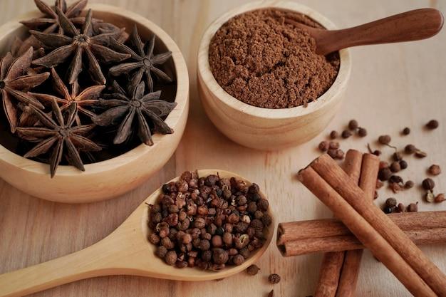 黒の背景、業界コンセプトの木製カップに粉末とスパイスを煮込む