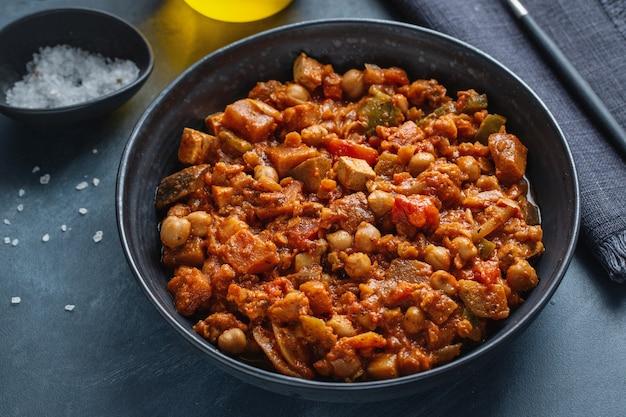 Stew vegetables ragout vegan with tofu served in bowl on dark.