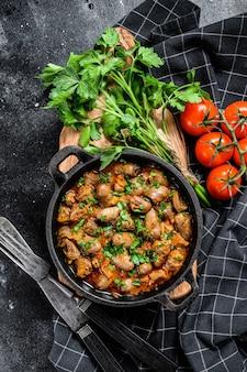 치킨 하트와 야채를 곁들인 신선한 파슬리를 끓입니다. 검정색 배경. 평면도.