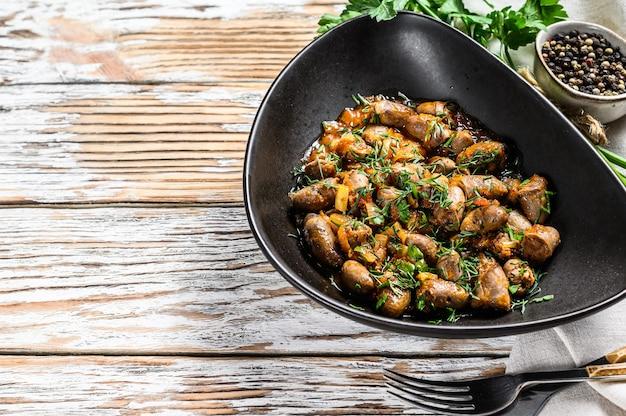 치킨 하트와 야채를 곁들인 신선한 파슬리를 끓입니다. 흰 배경. 평면도. 공간을 복사하십시오.