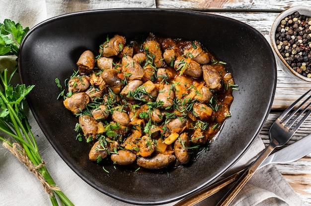 Тушить с куриными сердечками и овощами со свежей петрушкой. белый фон. вид сверху.