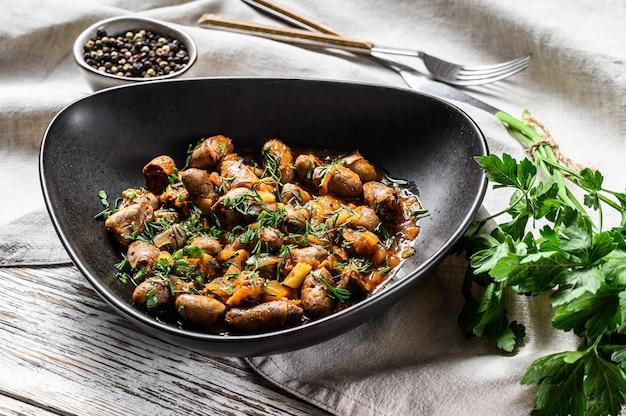 Рагу с куриными сердечками и овощами со свежей петрушкой. белый фон. вид сверху