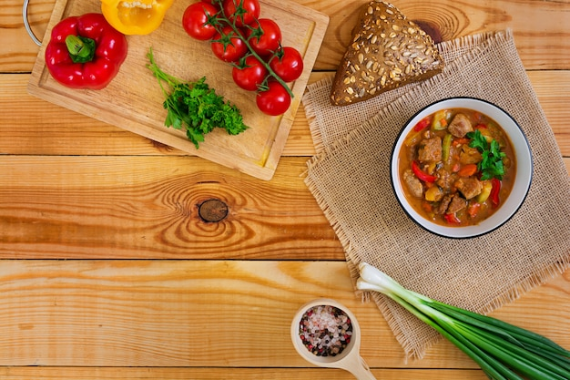 Stew with meat and vegetables in tomato sauce on wooden. top view