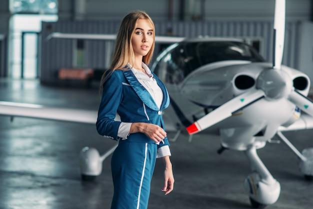Стюардесса против турбовинтового самолета в ангаре