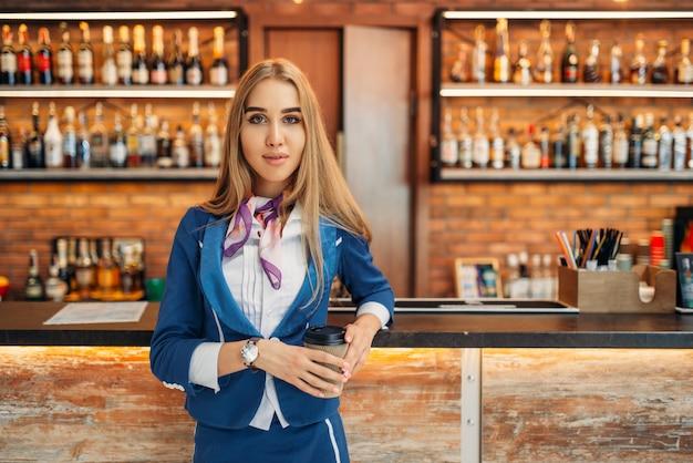 Стюардесса у стойки бара в кафе аэропорта