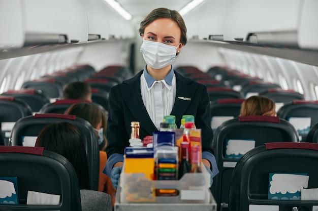 飛行機のジェット機の客室でフードトロリーを運ぶスチュワーデス。乗客がいる現代の飛行機のインテリア。ヨーロッパの女性は制服と医療用マスクを着用しています。民間航空。空の旅のコンセプト