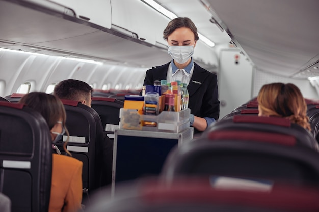 飛行機のジェット機の客室でフードトロリーを運ぶスチュワーデス。乗客がいる現代の飛行機のインテリア。ポジティブなヨーロッパの女性は制服と医療用マスクを着用しています。民間航空。空の旅のコンセプト