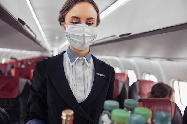 飛行機のジェット機の客室でフードトロリーを運ぶスチュワーデス。モダンな飛行機のインテリア。ヨーロッパの女性は制服と医療用マスクを着用しています。民間商用航空。空の旅のコンセプト