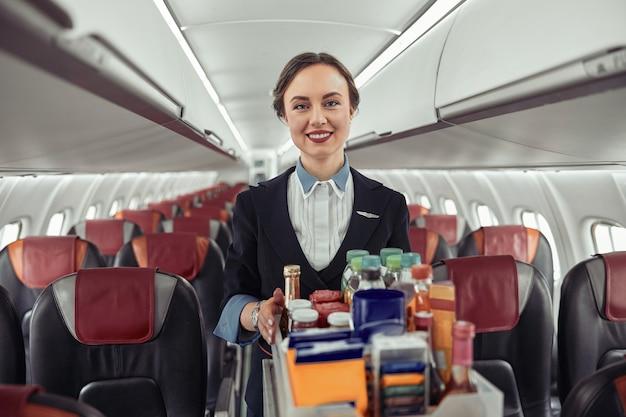 飛行機のジェット機の客室でフードトロリーを運ぶスチュワーデス。モダンな飛行機のインテリア。笑顔のヨーロッパの女性は制服を着てカメラを見ています。民間商用航空。空の旅のコンセプト