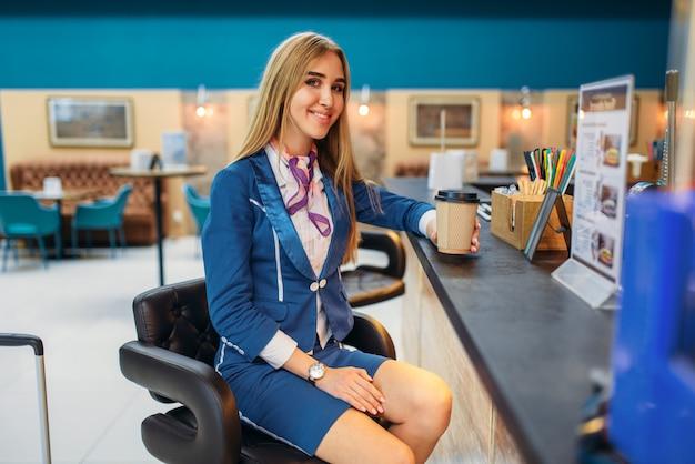 Стюардесса пьет кофе в кафе аэропорта