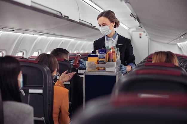飛行機のジェット機のキャビンで乗客に飲み物とボトルを与えるスチュワーデス。現代の飛行機のインテリア。フードトロリーを着たヨーロッパの女性は、制服と医療用マスクを着用しています。民間航空。空の旅のコンセプト