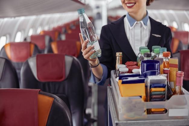 飛行機のジェット機の客室に水筒を持っているスチュワーデス。モダンな飛行機のインテリア。制服を着た女性のトリミング画像。民間商用航空。空の旅のコンセプト